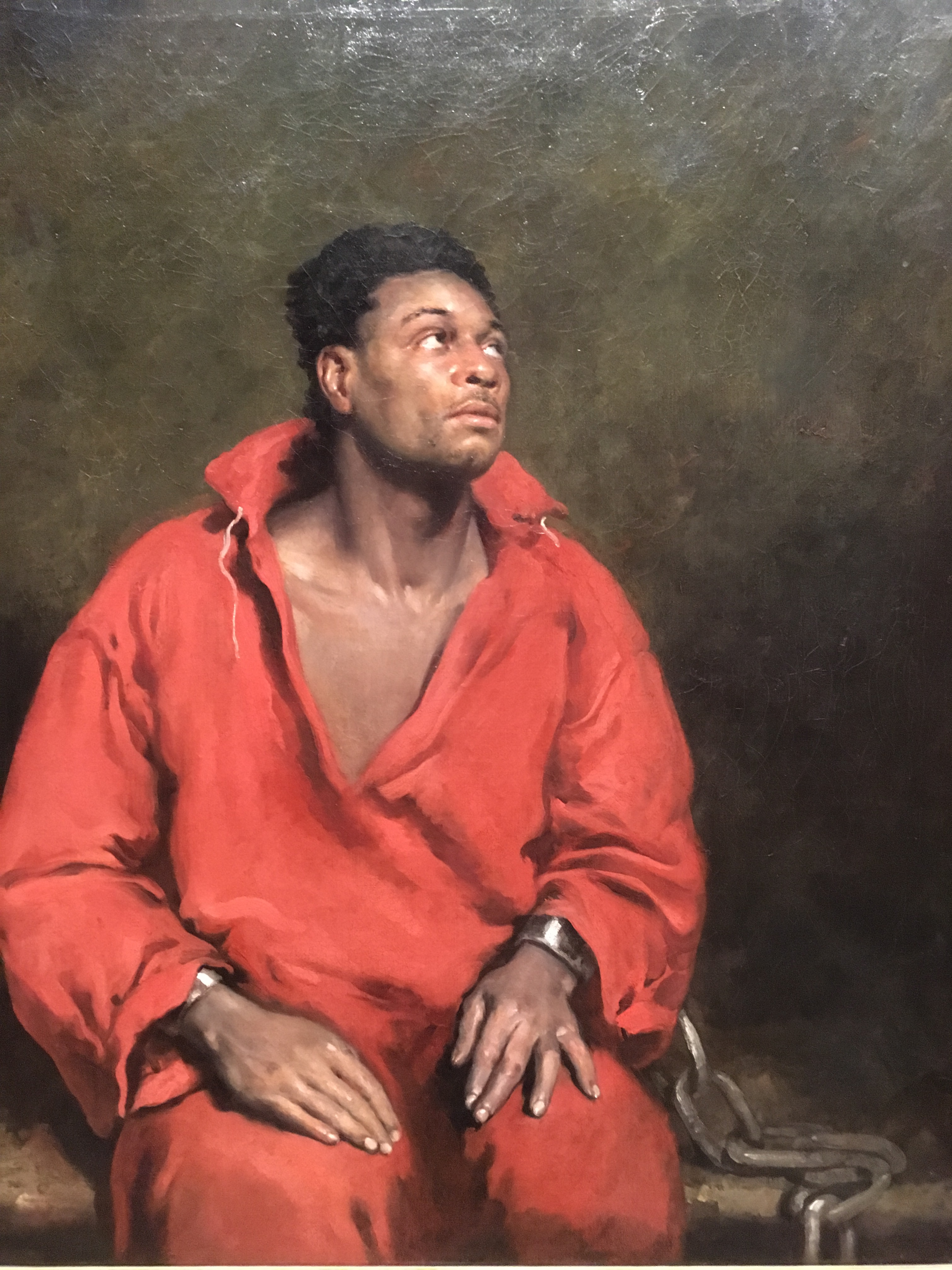 The captive slave:  A very powerful image.  Very sad expression. With almost a welling if tears in the eyes, the focus of the light informed us of his emotion. The detail in the hands is amazing—resigned.  Showing the body and dark surroundings gives us relevance.